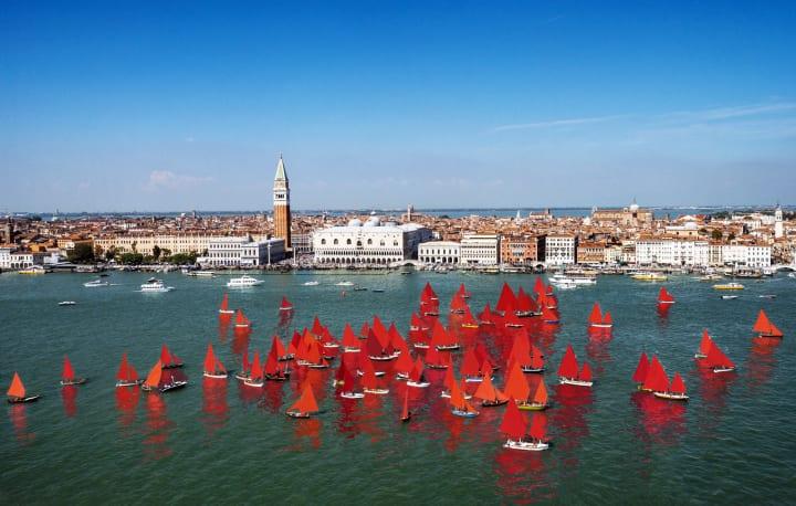 ヴェネツィアのパブリックアート「Red Regatta」 赤い帆の船団が気候変動とマスツーリズムに警鐘を鳴らす