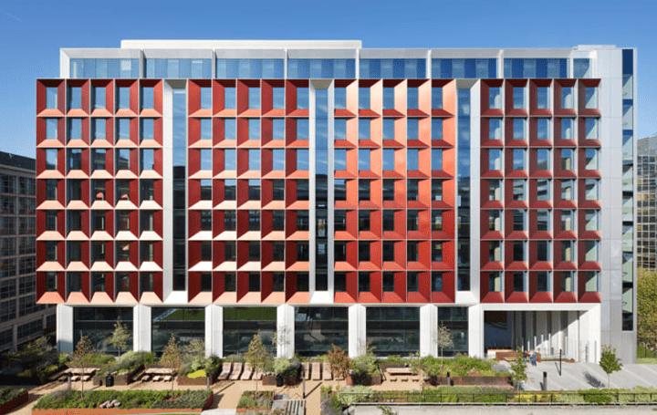 テラコッタの色合いに調和する赤が特徴の ロンドンのオフィスビル「245 Hammersmith Road」